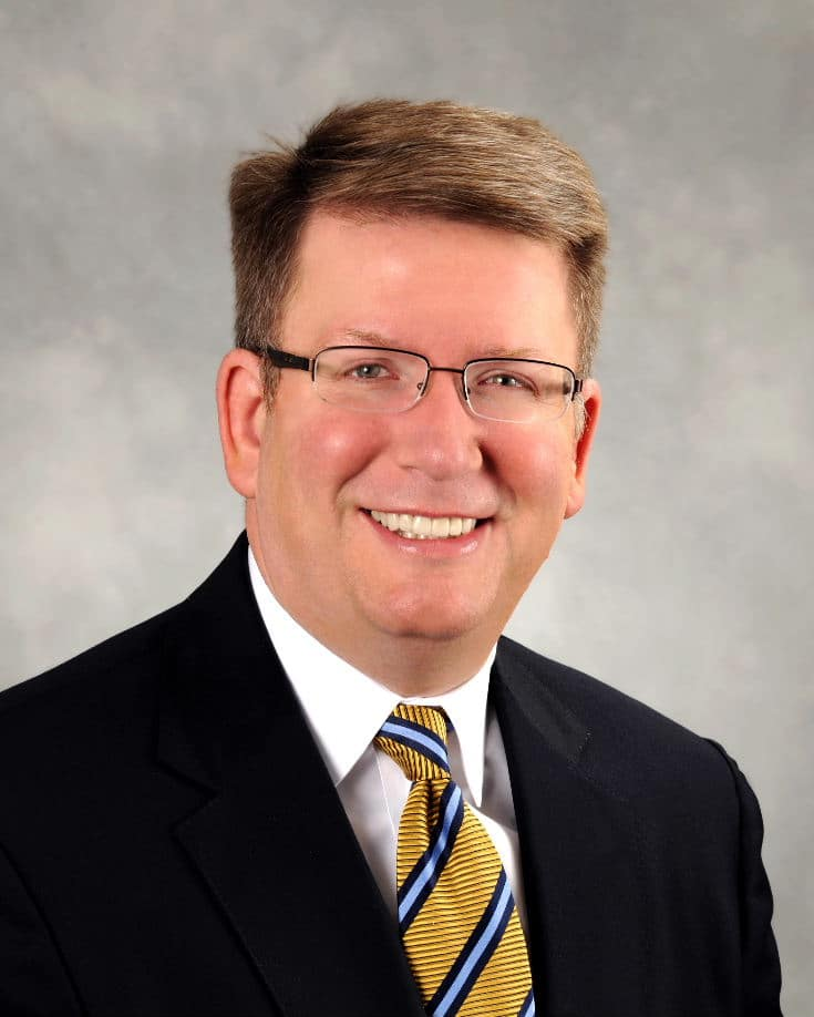 Photo of Pat Kelly in a yellow tie and black suit
